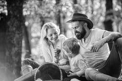 Moderfadern och den lilla sonen sitter skogpicknicken Bra dag f?r v?rpicknick i natur F?renat med naturen Familjdag royaltyfri fotografi