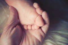 Moderhållen liten kal fot av behandla som ett barn lite flickan eller pojken Sova det nyfödda barnet Arkivfoton