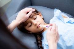 Moderhanden som tar temperatur med flickan, är sjukt lägga på soffan, ungepatient med mammakontrolltermometern royaltyfria bilder