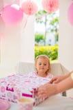 Moderhjälp som packar upp födelsedaggåva royaltyfri bild