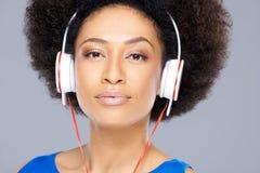 Moderiktig afrikansk amerikankvinna som lyssnar till musik Arkivfoto