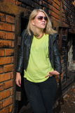Moderiktig blond flickabenägenhet mot en tegelstenvägg Arkivbilder