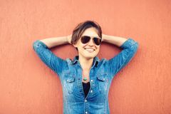 Moderiktig brunettflicka och att göra framsidauttryck, le och skratta mot orange bakgrund som isoleras modern livsstil Fotografering för Bildbyråer