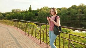 Moderiktig flicka i exponeringsglas genom att använda smartphonen i den europeiska staden Henne som utomhus står på bron Solnedgå lager videofilmer