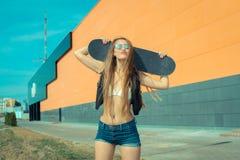Moderiktig flicka med skateboarden fotografering för bildbyråer