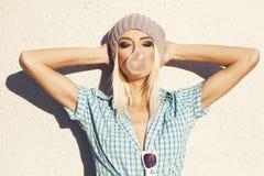 Moderiktig härlig blond modell och slagbubblegum Royaltyfria Bilder