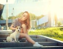 Moderiktig Hipsterflicka med hennes hund i staden Fotografering för Bildbyråer