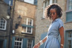 Moderiktig kvinna i blå korkad muffklänning och solglasögon royaltyfria foton