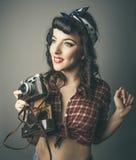 Moderiktig kvinna i 60-talöverkant med den retro kameran Arkivfoto