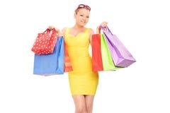 Moderiktig kvinna som rymmer en grupp av shoppingpåsar Fotografering för Bildbyråer