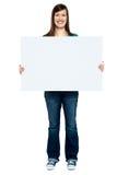 Moderiktig kvinna som visar den blanka affischtavlan till kameran Royaltyfri Fotografi