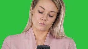 Moderiktig le blond kvinna som använder hennes mobiltelefon som ler, som hon skriver ett textmeddelande på en grön skärm, Chromat arkivfilmer