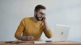 Moderiktig man som talar på telefonen och skriver en rapport arkivfilmer