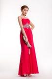 Moderiktig modemodell i långt rött posera för klänning Royaltyfri Fotografi