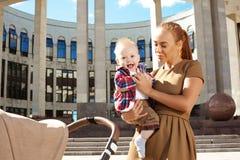 Moderiktig modern moder på en stadsgata med en pram. Barnmoder Arkivbild