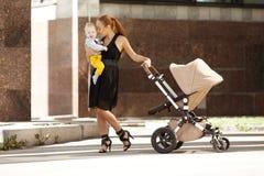 Moderiktig modern moder på en stadsgata med en pram. Barnmoder Fotografering för Bildbyråer