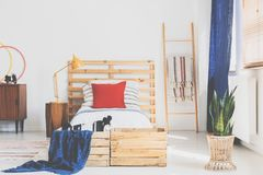 Moderiktig retro design i sovrum med trämöblemang och den vita väggen, verkligt foto royaltyfri fotografi