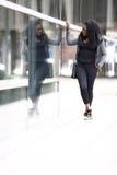 Moderiktig ung afrikansk kvinna som beundrar hennes reflexion fotografering för bildbyråer
