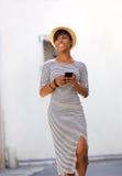 Moderiktig ung kvinna som går med mobiltelefonen Arkivbilder
