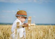 Moderiktig ung pojke som spelar i ett fält med en nivå Arkivfoto