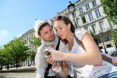 Moderiktiga par i stad genom att använda smartphonen Arkivfoton