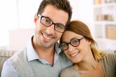 Moderiktiga par med glasögon som kopplar av i soffa Royaltyfri Foto