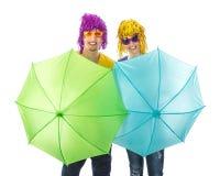 Moderiktiga par med solglasögon och peruker som skyddas av paraplyer Arkivfoto