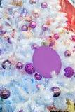 Moderiktiga purpurfärgade ultravioletta kulöra struntsaker försilvrar på den vita konstgjorda julgranen close upp Selektiv fokus, arkivfoto