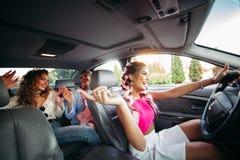 Moderiktiga, stilfulla moderiktiga flickvänner går i bilen som tillsammans lyssnar till musik och har gyckel De går att shoppa fö Royaltyfri Foto