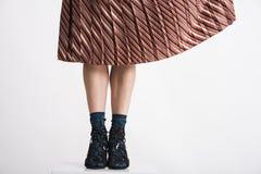 Moderiktiga ung kvinnas ben med den fladdra kjolen för aery royaltyfri foto
