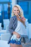 Moderiktigt foto av den ursnygga unga damen med blont lockigt hår och ljus makeup, i stilfull modern klänning av jeans och godisb royaltyfri foto
