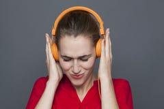 Moderiktigt hörlurarbegrepp för fokuserad 20-talflicka Royaltyfri Foto