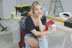Moderiktigt kvinnligt sammanträde på snickarearbetsbänken Royaltyfri Fotografi