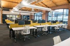 Moderiktigt modernt öppet utrymme för begreppsvindkontor med stora fönster, naturligt ljus och en orientering som uppmuntrar sama arkivfoton
