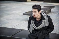 Moderiktigt stiligt sammanträde för ung man på stenbänk Arkivfoton
