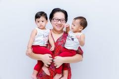 Moderinnehav två behandla som ett barn pojkar Stor lycka, den lyckliga unga mamman med två kopplar samman behandla som ett barn S arkivfoto