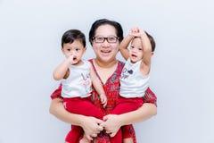 Moderinnehav två behandla som ett barn pojkar Stor lycka, den lyckliga unga mamman med två kopplar samman behandla som ett barn S royaltyfri fotografi