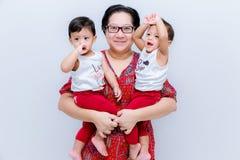 Moderinnehav två behandla som ett barn pojkar Stor lycka, den lyckliga unga mamman med två kopplar samman behandla som ett barn S arkivfoton