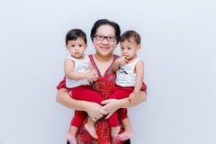 Moderinnehav två behandla som ett barn pojkar Stor lycka, den lyckliga unga mamman med två kopplar samman behandla som ett barn S royaltyfri foto