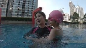 Moderinnehavdotter som undervisar henne att simma stock video