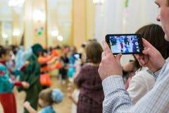 Moderinspelningbarn på telefonen Arkivfoto
