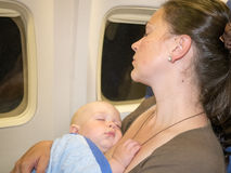 Moderkramen och sömn med hennes nyfött behandla som ett barn under flyg Begreppsfoto av flygresan Royaltyfria Foton