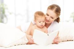 Moderläseboken behandla som ett barn i säng Royaltyfri Fotografi