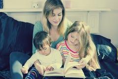 Moderläsning till ungar i säng fotografering för bildbyråer