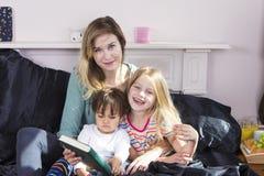 Moderläsning till ungar i säng royaltyfri foto