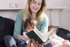 Moderläsning till ungar i säng arkivfoto