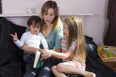 Moderläsning till ungar i säng arkivbilder