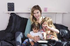 Moderläsning till ungar i säng royaltyfri bild
