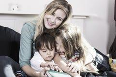 Moderläsning till ungar i säng royaltyfria foton