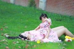 Moderleklekar med hennes litet behandla som ett barn flickan på gräsmattan Royaltyfria Foton